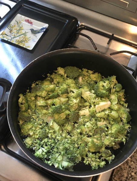 broccoli in a pot of water boiling on a stove top